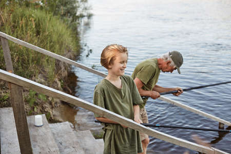 Father and son fishing together, standing on wooden stairs leading to water, grandson with his grandpa having fun in open air, enjoying beautiful nature and silence.
