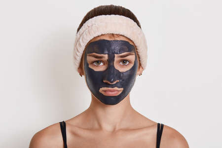 Young beautiful woman in black mud mask for face doing cosmetic procedures, looks sad, posing against white wall, wearing hair band, looks at camera.