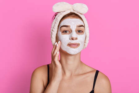 Attractive confident female with cosmetic facial mask on face has beauty treatment, looking directly at camera and touching her cheek, posing against pink wall.