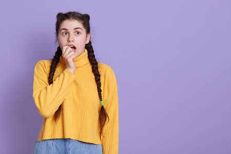 Closeup photo of attractive scared lady two pigtails biting fist, looks at camera, feel guilty terrified, wears casual white yellow jumper, isolated over lilac background. Copy space. Archivio Fotografico - 151724689