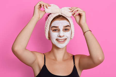 Adorable funny woman with clay mask on her face and hair band with bow on head touching her headband and looking at camera, has beauty procedures at home in morning. Archivio Fotografico