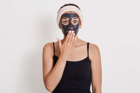 Emotional surprised Caucasian woman looks with shocked expression directly at camera, stands against white background, cleans her skin with mud cosmetic mask. Archivio Fotografico - 151724695