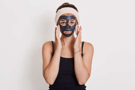 Young unhappy housewife with black cosmetic mask on face standing isolated over white background, touching her cheeks with fingers, looking at camera. Archivio Fotografico - 151724701