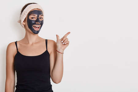 Positive female applies nourishing mask on face, pointing fore finger aside on copy space, undergoes beauty treatments, poses indoor against white wall. Copy space. Archivio Fotografico - 151724703