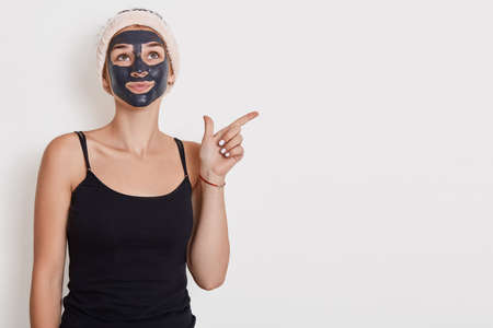 Thoughtful woman looks pensively up, applies black mask on face, wears hairband and sleeveless t shirt, points away at empty space isolated over white background