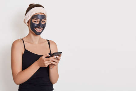 Girl in white hairband on her head and in clay black face mask holds mobile phone and writing message or reads news, doing beauty treatments at home, facial skin care.