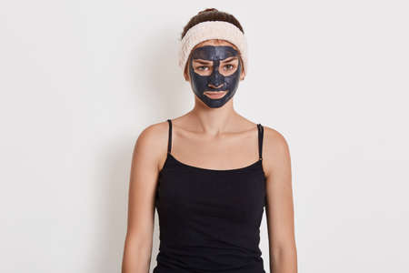 Beautiful girl with clay mask on her face standing with upset facial expression, looking at camera with sadness, wearing black t shirt and hairband.