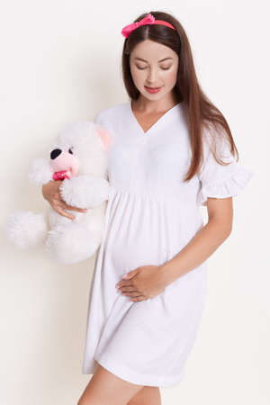 Lovely pregnant girl with teddy bear wearing white dress, dark haired female with soft bear, touching her belly and looking on it, looks happy and gently. Archivio Fotografico - 151724781