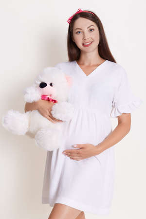 Pregnancy with teddy bear wearing beautiful dress and rose hair band with bow, looking smiling at camera, posing against white background, looks happy and gently.