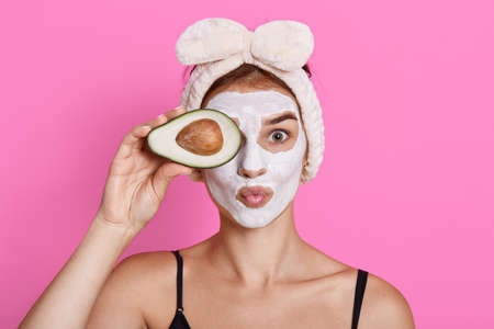 Cheerful woman with cosmetic mask on face, doing spa treatment, covering eye with half of avocado, keeping lips rounded isolated on pink background, has perfect fresh skin. Archivio Fotografico - 151725002