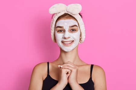 Winsome smiling brunette woman in funny hairband on head applying white nourishing mask or creme on face isolated over background, keeps hands together in front of chest. Archivio Fotografico - 151725005
