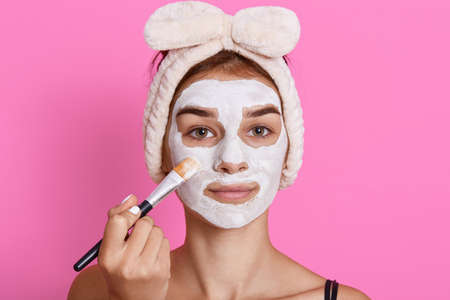 Attractive female applying clay facial mask on her face, looking directly at camera with calm facial expression, having funny hairband on head, doing beauty treatment.