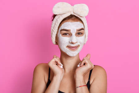 Young woman with clay mask on her face posing against rosy background, cheerful girl doing skin care manipulations at home, being in good mood, keeping fists near face. Archivio Fotografico