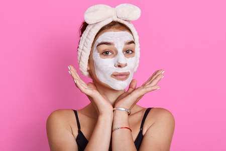 Adorable woman has glad look, keeps hands under chin, looks directly at camera, hydrates and calms skin, wears fanny hairband with bow on head. Archivio Fotografico - 151725011