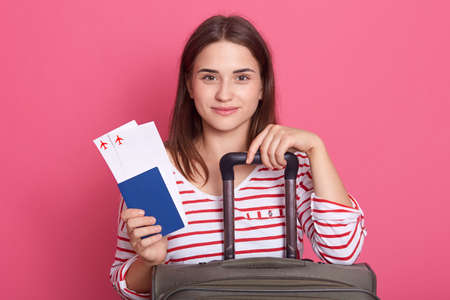 Happy woman girl with suitcase, ticket and passport posing isolated over pink background, dark haired female wearing striped casual shirt travels abroad. 스톡 콘텐츠
