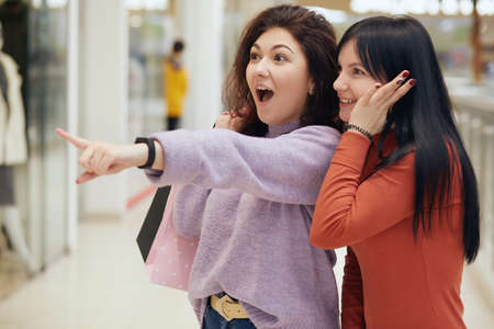 Two excited young women with shopping bags shouting and talking emotionally while pointing at window displays in shopping mall on sales day, attractive ladies in casual attire being astonished.