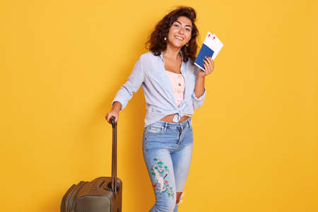 Full length portrait of happy woman with suitcase tickets and passport posing on yellow background, looks happy, has summer tour and being hurry to airport.