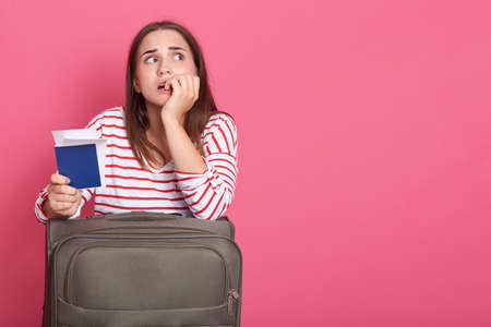 Confused young woman posing isolated rosy background, holding passport with tickets and suitcase, looking up with upset and tired facial expression. 스톡 콘텐츠