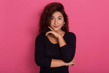 Photo of lovely female keeps hand under chin, posing with good emotions, wearing black shirt, standing isolated over pink background, stylish lady with make up.