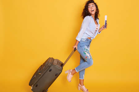 Full length shot of female in casual clothing walking with travel bag and documents, traveling abroad, has vacation in resort, waiting her plane, looks happy. 스톡 콘텐츠