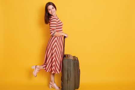Happy woman with perfect body standing with travel suitcase, wearing elegant striped dress posing on one leg looking at camera isolated over yellow wall. 스톡 콘텐츠