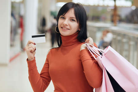 Portrait of attractive caucasian young woman with credit card in hand with shopping bags, in the city, brunette female looking directly at camera.