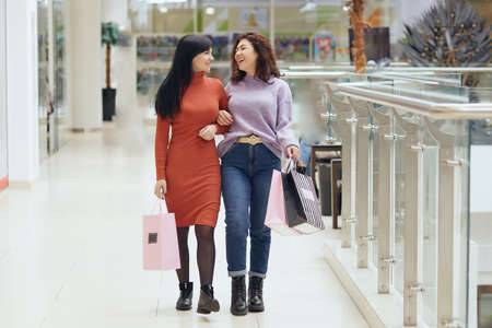 Attractive happy young women in shopping mall walking and smiling, holding shopping bags, spending time together, buying new clothing, expressing positive emotions.