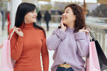 Two friends doing shopping in mall, posing with astonished and excited, looking at each other with smile, buying new dresses, holding shopping bags.