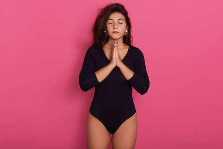 Beautiful young Caucasian woman stands in meditative pose, enjoys peaceful atmosphere, holds hands in praying gesture, isolated over pink background, wearing black bodysuit.