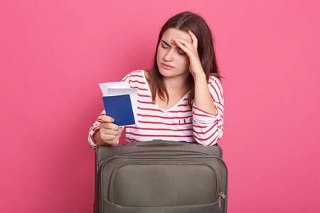 Photo of woman dressed striped shirt on pink background, looks tired and exhausted, waiting her plane for long hours, posing with suitcase, passport and tickets, looks at documents with sad expression