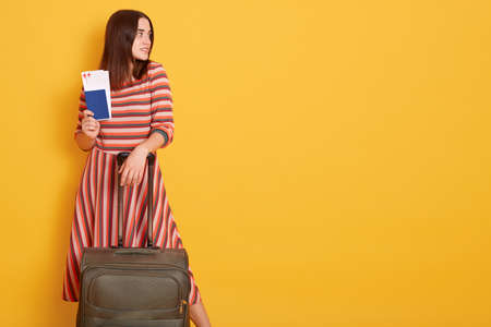 Attractive lady wearing striped dress holding passport and tickets, stands with suitcase against yellow wall and looking aside, visits popular destination. 스톡 콘텐츠