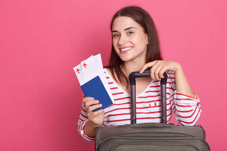 Portrait of nice attractive elegant feminine cheerful lady boarding, holding passport and ticket, has vacation, isolated on pink background, looks happy. 스톡 콘텐츠