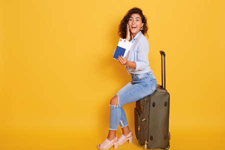 European woman with passport and ticket sitting on suitcase and looking happy and excited, keeps mouth opened and touching her cheek with palm, girl has annual vacation.