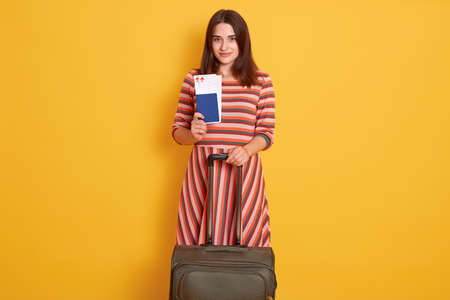 Photo of pretty lady traveler holding passport, tickets and rolling suitcase luggage being in airport, being ready to travel abroad, model against yellow wall.