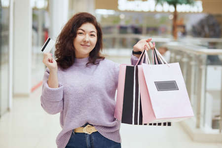 Charming lady wearing lilac sweater holding credit card and shopping bags in hands posing in shopping mall, standing with her purchases, doing shopping, pays with credit card. 스톡 콘텐츠