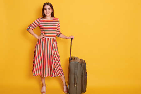 Full length of woman in elegant dress standing with suitcase isolated over yellow background, keeping hand on hip, looking at camera, being ready travels abroad.