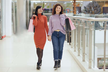 Full length portrait of young females posing in mall with shopping bags, women wearing casual attires, holding hands, expressing happiness, buying new attires.