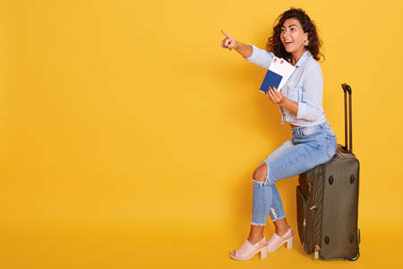 Smiling girl in stylish clothing isolated over pink background. Passenger traveling abroad, has air flight journey, holding passport and ticket while sitting on suitcase, pointing index finger aside.