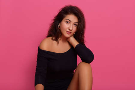 Gentle romantic female with confident look posing against pink wall, looking at camera, wearing black combi dress, keeping hand on her neck, attractive girl with bare shoulders.