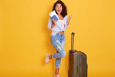 Funny happy girl posing on one leg near suitcase, holding passport with flight tickets, isolated over yellow background, clenching fists and looks happy.