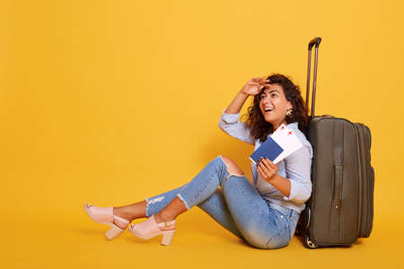 Portrait of tourist woman waiting for flight, sitting on floor near her suitcase, holding documents in hand isolated over yellow background, keeping hands near forehead and looking in distance.