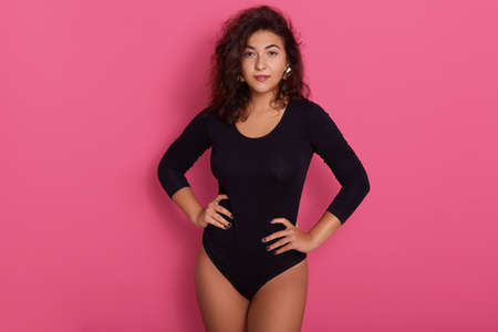 Brunette female with hands on her hips, having wavy hair, posing isolated over rosy background, attractive girl wearing black bodysuit, looking directly at camera, looks confident.
