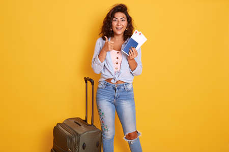 Woman standing isolated over yellow background holding passport and ticket, standing near suitcase and showing thumb up, being ready to boarding plane.