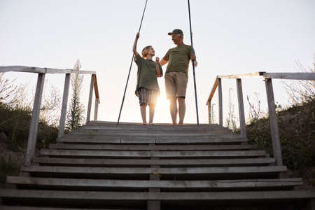 Father and son go to fishing place, holding fishing rods, family enjoying spending time together during beautiful sunset, looking at each other while posing on wooden stairs leading to water.