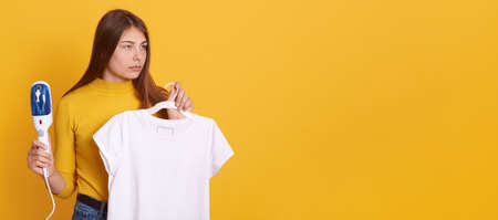Young woman steaming her clothes at home, holding steam iron and white t shirt on hangers in hands, looking aside with serious look, posing against yellow wall. Stock Photo