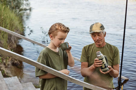 Concentrated man with his blond son drinking tea from, standing outdoors with river view, spending summer day together near lake, dad with son enjoying hot beverage.