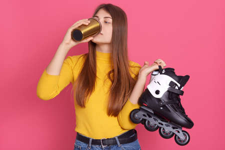 Adorable female skaters drinking hot coffee or tea from stylish thermo mug, holding rolling skate in hands, lady with long hair posing against pink background.