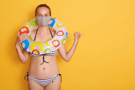 Attractive young woman in swimsuit with rubber ring in medical mask isolated over yellow background, pointing aside with thumb, copy space for advertisement. 스톡 콘텐츠