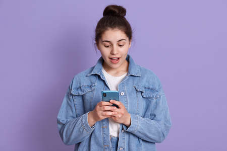 Portrait of astonished woman with modern smart phone in hands, dresses stylish outfit, looking at screen of mobile phone with amazed expression, isolated over lilac background. 스톡 콘텐츠