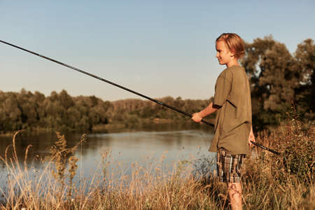 Little boy holding fishing pole in hands, wearing green t shirt and cap, blond male kid fishing at bank of river, looks concentrated, wants to catch fish. 스톡 콘텐츠